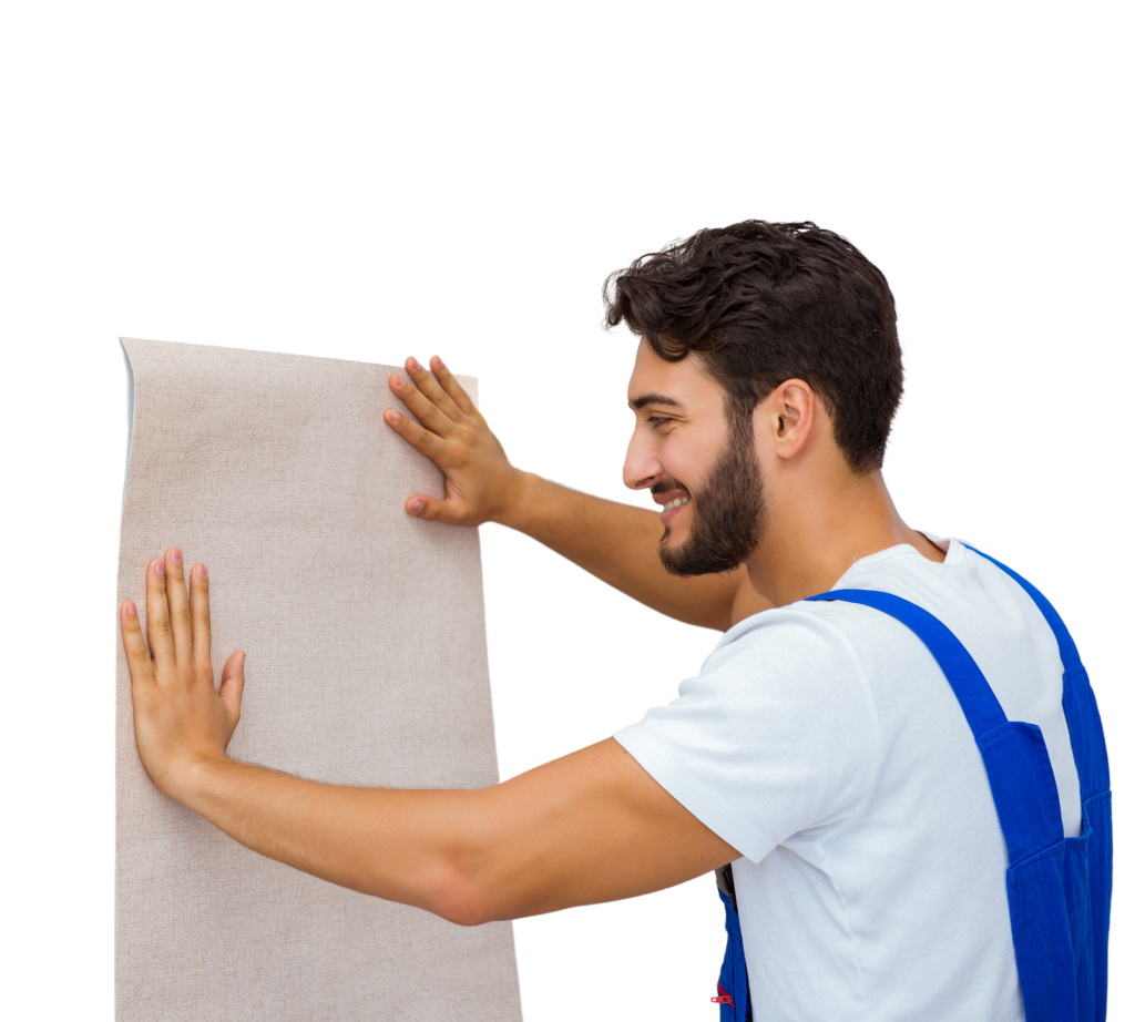 A smiling man with a beard wears a pair of blue overalls while hanging wallpaper