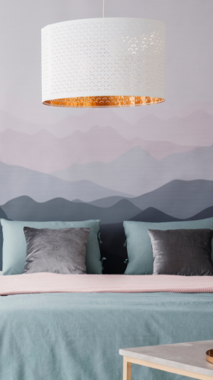 A serene bedroom with a misty mountain wallpaper behind the headboard of a teal and grey bed. You can tell they got their wallpaper installaed by Miramar Wallpaper!