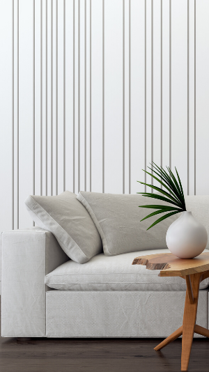 a white vase sits on a raw wood table in front of a white couch. The wallpaper is white with grey vertical stripes set asymmetrically apart