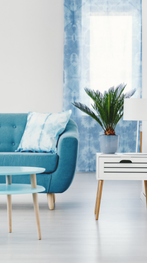 a blue couch sits in front of pretty blue wallpaper
