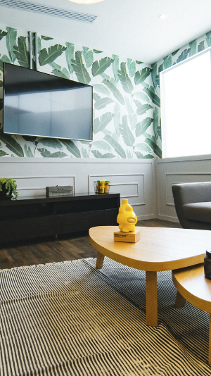 looking into a corner of a room where there is a window on the right and a TV on the left. Behind the TV is a wallpaper with a white background with large green banana leaves.