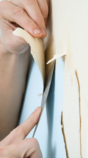 Close up of hands removing blue wallpaper with a putty knife