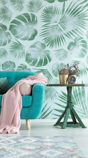 A stylish teal couch with a pink blanket sits next to a table with plants on it. The wall is covered in wallpaper with large green leaves on a white background.